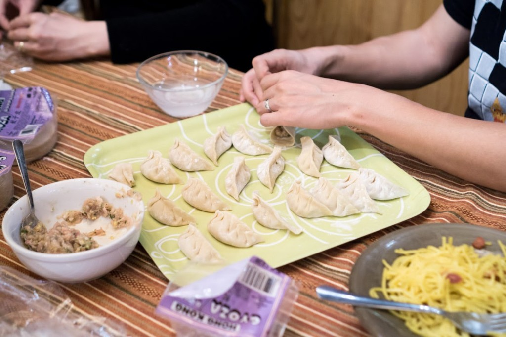 Wrapping dumplings with packaged dumpling dough. Notice the unique s-shaped style in the middle of the platter.