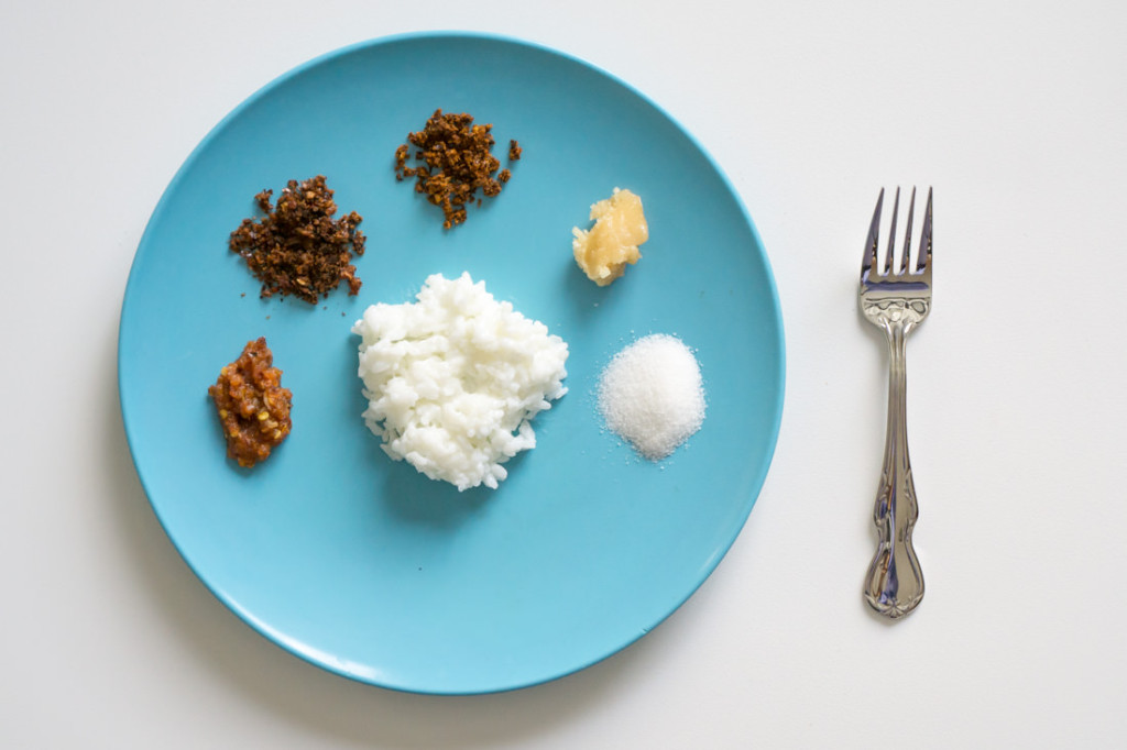 Kiribath breakfast, from left to right: lunu miris (katta sambol), Maldive fish sambol, Zensai Chilli Paste, jaggery (coconut palm sugar), granulated sugar, and kiribath in the center